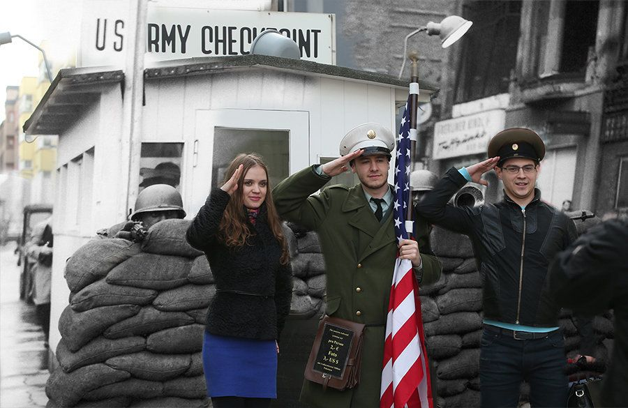 Young visitors from Russia pose for a photo with an actor dressed as a U.S. soldier at the former Checkpoint Charlie border c
