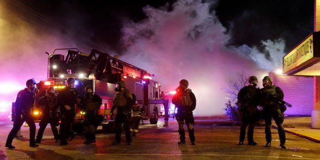 Smoke fills the streets as some buildings are on fire after the announcement of the grand jury decision Monday, Nov. 24, 2014