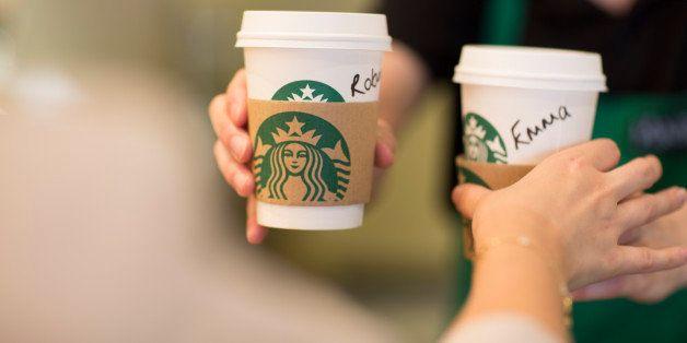 An employee, right, hands a customer personalised cardboard coffee cups inside a Starbucks Corp. coffee shop in London, U.K.,