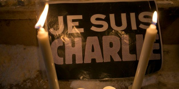 """Candles are lit near a sign that read in French """"I am Charlie"""" lights a candle during a demonstration in solidarity with thos"""