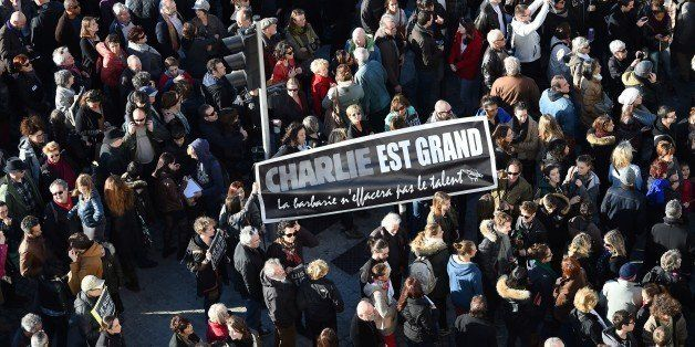 A people holds a sign reading 'Charlie is great, barbarism won t erase talent' during a demonstration attended by an estimate