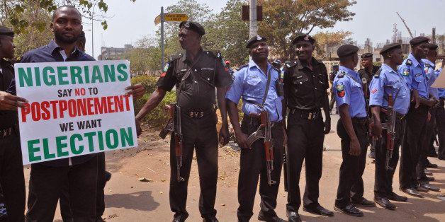 Nigerian Police provide security in Abuja, Nigeria, Saturday, Feb. 7, 2015, as people demonstrate against the possible postpo