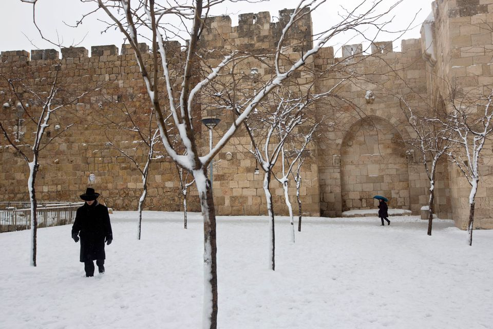 An ultra-Orthodox Jewish man walks in the snow near the Jaffa gate in Jerusalem's Old City, Friday, Feb. 20, 2015. (AP Photo/
