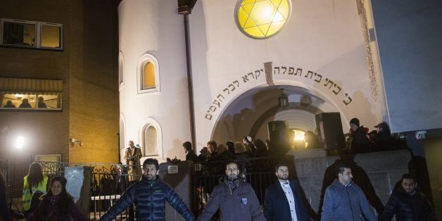 Norwegian Muslims create a human peace ring around the synagogue in Oslo, Norway on February 21, 2015. More than a 1,000 join