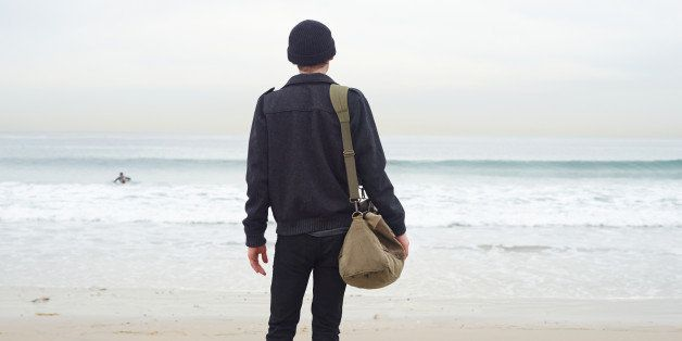 Man carrying luggage and looking at shore