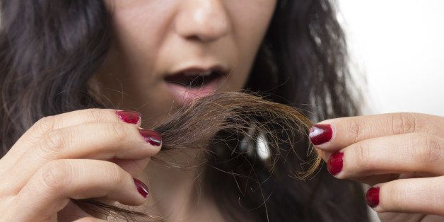 Girl looking at damaged splitting ends of hair.