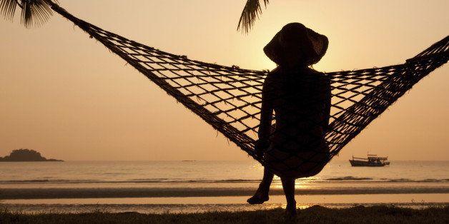 woman in hammock enjoying sunset on the beach