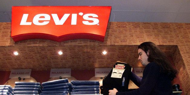 Store employee Brett Mitsobata stocks a Levi's jeans display at a downtown Toronto department store Monday, Feb. 22, 1999. Le