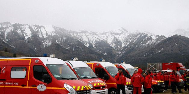 Rescue workers stand by ambulances at Seyne les Alpes, French Alps, Tuesday, March 24, 2015. A Germanwings passenger jet carr