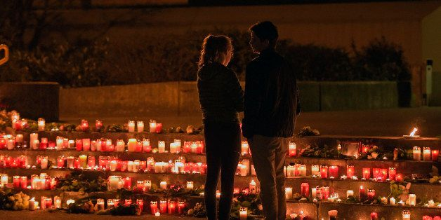 Students stand in front of candles in front of the Joseph-Koenig Gymnasium in Haltern, western Germany Tuesday, March 24, 201
