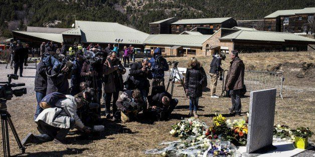 Journalists gather around a stele, carved in French, German, Spanish and English, in memory of the victims of the Germanwings Airbus A320 crash, in the small village of Le Vernet, French Alps, on March 27, 2015, near the site where an Airbus A320 crashed on March 24. The Germanwings co-pilot who flew his Airbus into the French Alps, killing all 150 aboard, hid a serious illness from the airline, prosecutors said on March 27 amid reports he was severely depressed. AFP PHOTO / JEFF PACHOUD        (Photo credit should read JEFF PACHOUD/AFP/Getty Images)