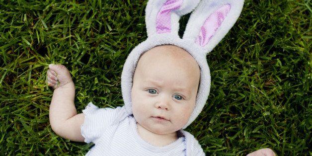 Baby lying in grass wearing Easter bunny ears