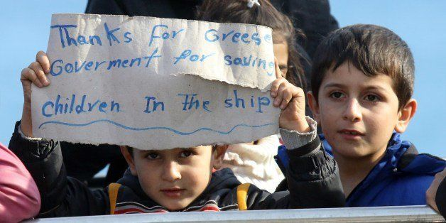 Migrant children display on November 27, 2014 a sign upon their arrival in the Cretan port of Ierapetra. Around 700 migrants