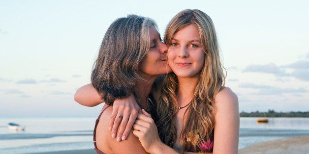 Mother and daughter (14-15) hugging on