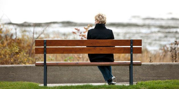 Mature woman sitting alone on park bench.