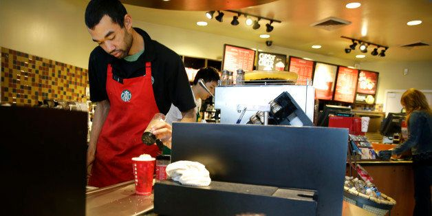 FILE - In this Nov. 24, 2014, file photo, barista Jay Rapp prepares a Chestnut Praline Latte at a Starbucks store in Seattle.