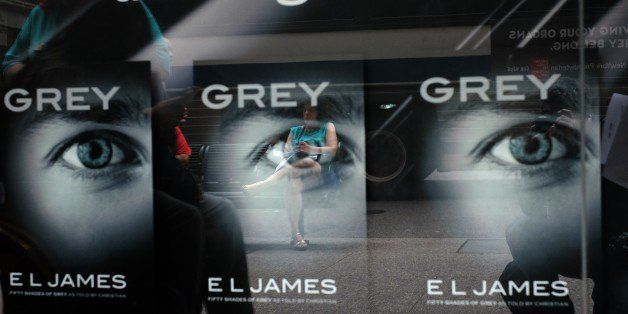 A woman sitting on a bench is reflected on a glass window advertising E.L James's new book 'Grey: Fifty Shades of Grey as Tol