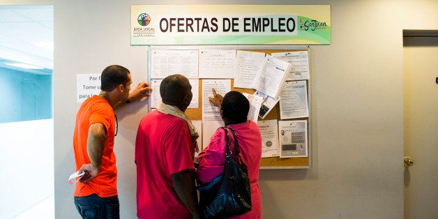 SAN JUAN, PUERTO RICO - NOVEMBER 14:  People scan the bulletin board for job postings at the unemployment office on November