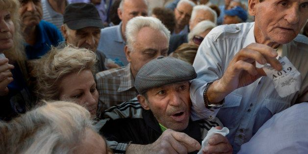 Pensioners holding their queue numbers try to enter into a bank in Athens, Wednesday, July 1, 2015. About 1,000 bank branches