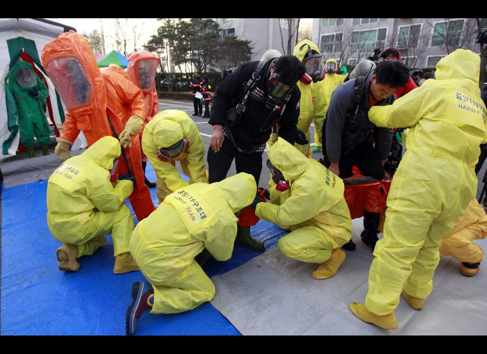 South Korean hazmat team members wearing anti-chemical suits prepare a civil defense drill from a possible North Korea's chem