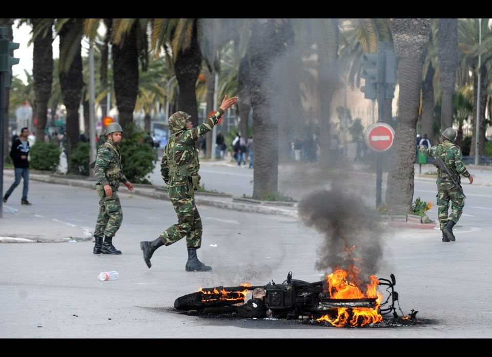 Tunisian security forces personnel walk past a burning motorcycle during clashes with demonstrators in Mohamed V avenue in Tu