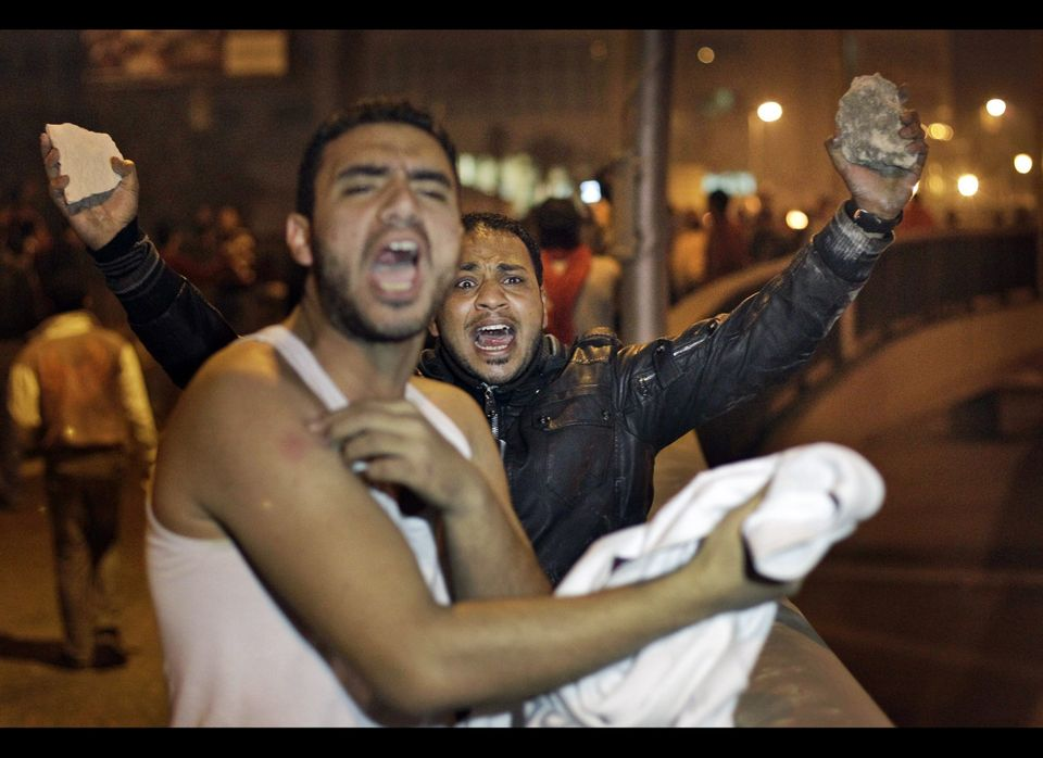 A protester holds rocks in the air, ready to throw at riot police, as he urges other protesters on, while another protester s