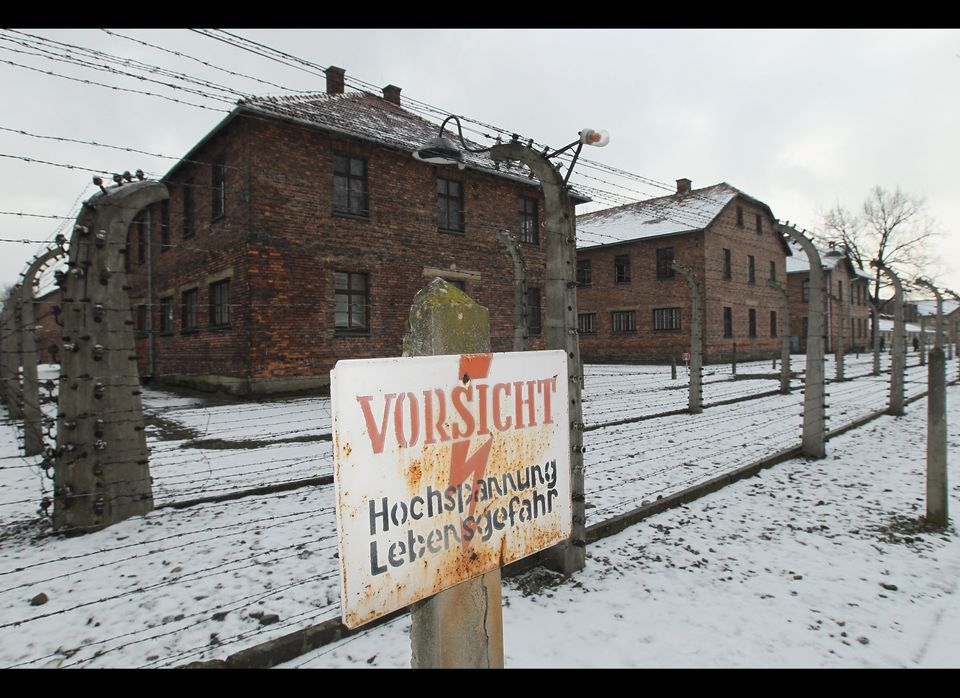 "A sign in German reads: ""Careful, High-Voltage, Danger"" at the former electrified perimeter fence at the Auschwitz I memorial"