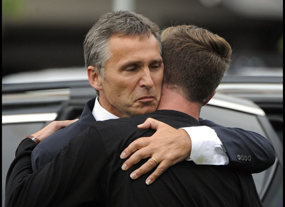 Norwegian Prime Minister Jens Stoltenberg (L) reacts as he embraces Eskil Pedersen, the leader of the Norwegian Labour Youth