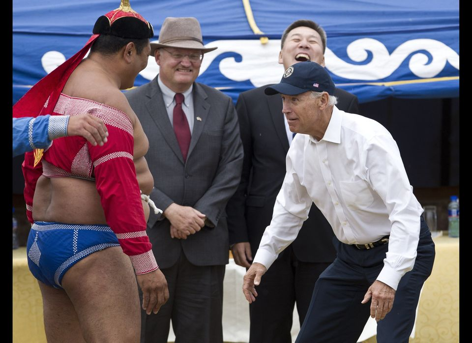 U.S. Vice President Joe Biden, right, meets Mongolian wrestler during Mini Nadam or Mongolian wrestling performance in Ulan B
