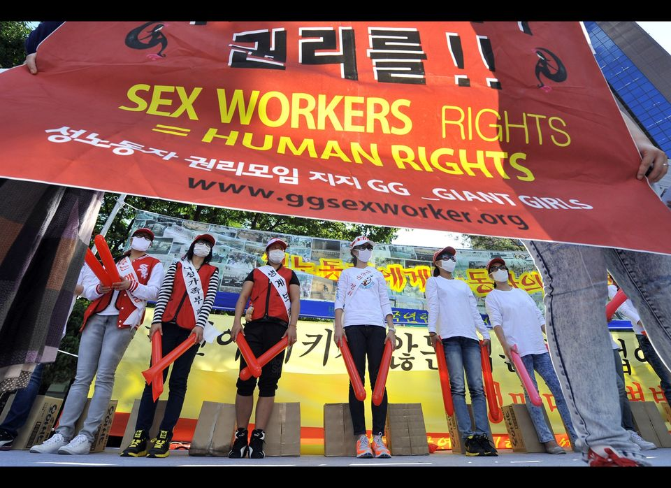 South Korean women working in the sex industry stand on a stage during a rally in central Seoul on September 22, 2011 in prot