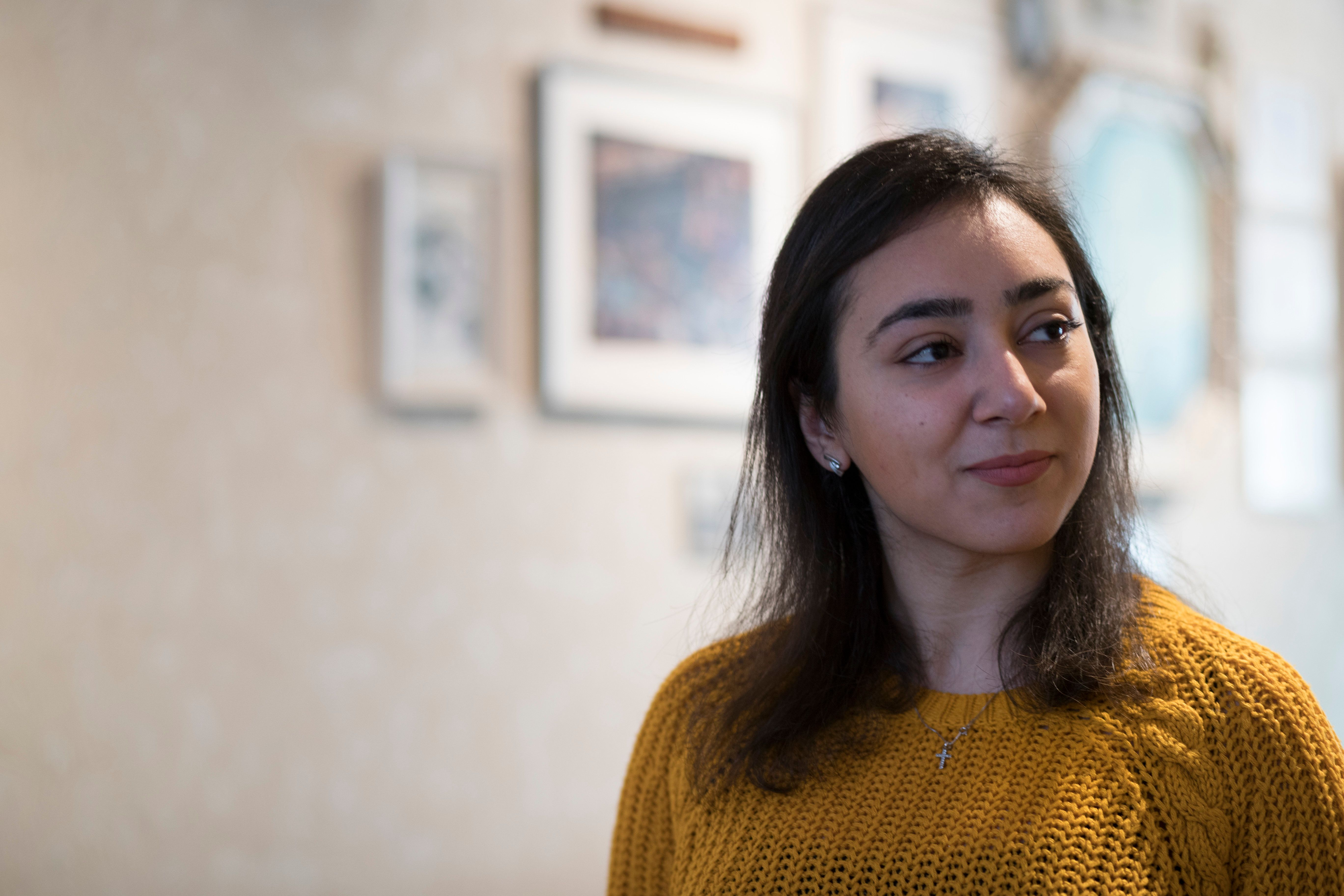 Hayarpi Tamrazyan, a 21-year-old Armenian asylum seeker, reads a poem she wrote during a press conference inside the Bethel chapel in The Hague, Netherlands, Thursday, Dec. 13, 2018. For more than 6 weeks, a rotating roster of preachers and visitors has been leading a non-stop, round-the-clock service at a small Protestant chapel in a quiet residential street in The Hague in an attempt to prevent the deportation of the Tamrazyan family. (AP Photo/Peter Dejong)