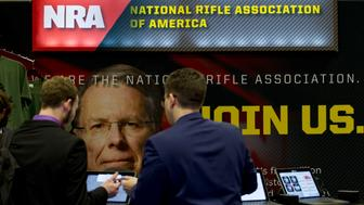 People gather at the NRA booth during the Conservative Political Action Conference, CPAC 2019, in Oxon Hill, Md., Friday, March 1, 2019. (AP Photo/Jose Luis Magana)