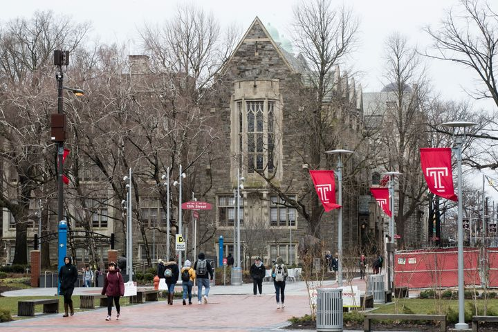 People walk on the Temple University campus in Philadelphia on Friday. Philadelphia health officials say scores of people hav
