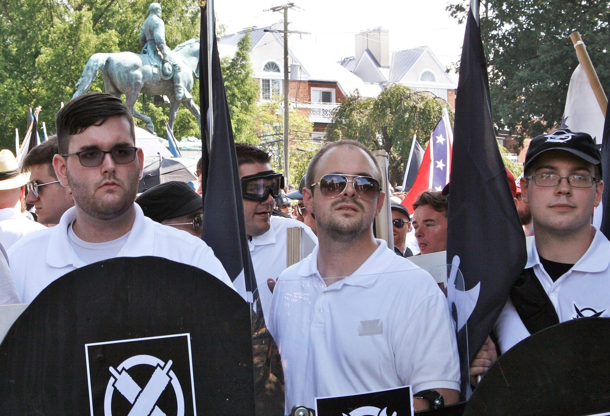 FILE - In this Saturday, Aug. 12, 2017, file photo, James Alex Fields Jr., left, holds a black shield in Charlottesville, Va., where a white supremacist rally took place. Fields Jr., of Maumee, Ohio, is charged with first-degree murder for allegedly driving his car into a crowd of people protesting against white nationalists. A 32-year-old woman was killed and dozens more were injured. (Alan Goffinski via AP, File)