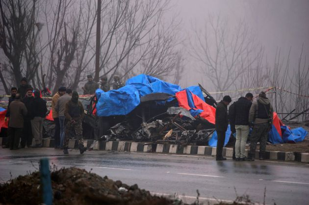 Forensic officials inspect the wreckage after the Pulwama