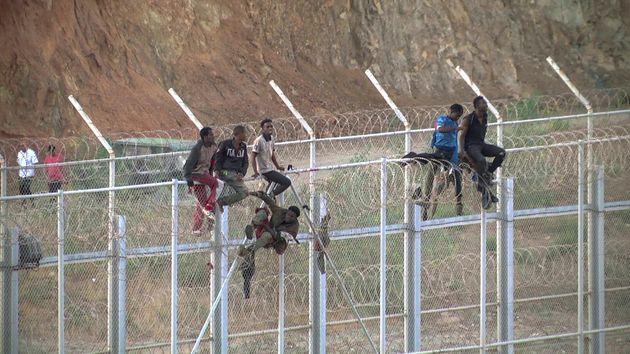 Des migrants subsahariens franchissent la frontière séparant le Maroc de l'Espagne, à...