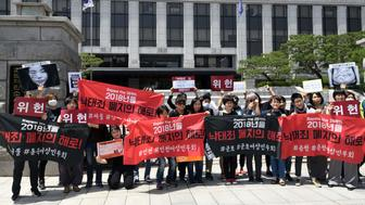 South Korean pro-choice supporters hold banners reading 'Decriminalize abortions' during a rally in front of the Constitutional Court in Seoul on May 24, 2018. - South Korea is one of the few industrialised nations where the abortion is illegal except for instances of rape, incest and when the mother's health is at risk. The Constitutional Court is due to review a challenge from a doctor who was prosecuted for performing nearly 70 abortions on May 24. (Photo by Jung Yeon-je / AFP)        (Photo credit should read JUNG YEON-JE/AFP/Getty Images)