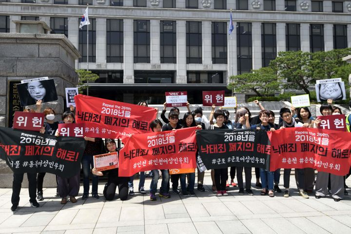 "South Korean pro-choice supporters hold banners reading ""Decriminalize abortions"" during a rally in front of the Constitution"