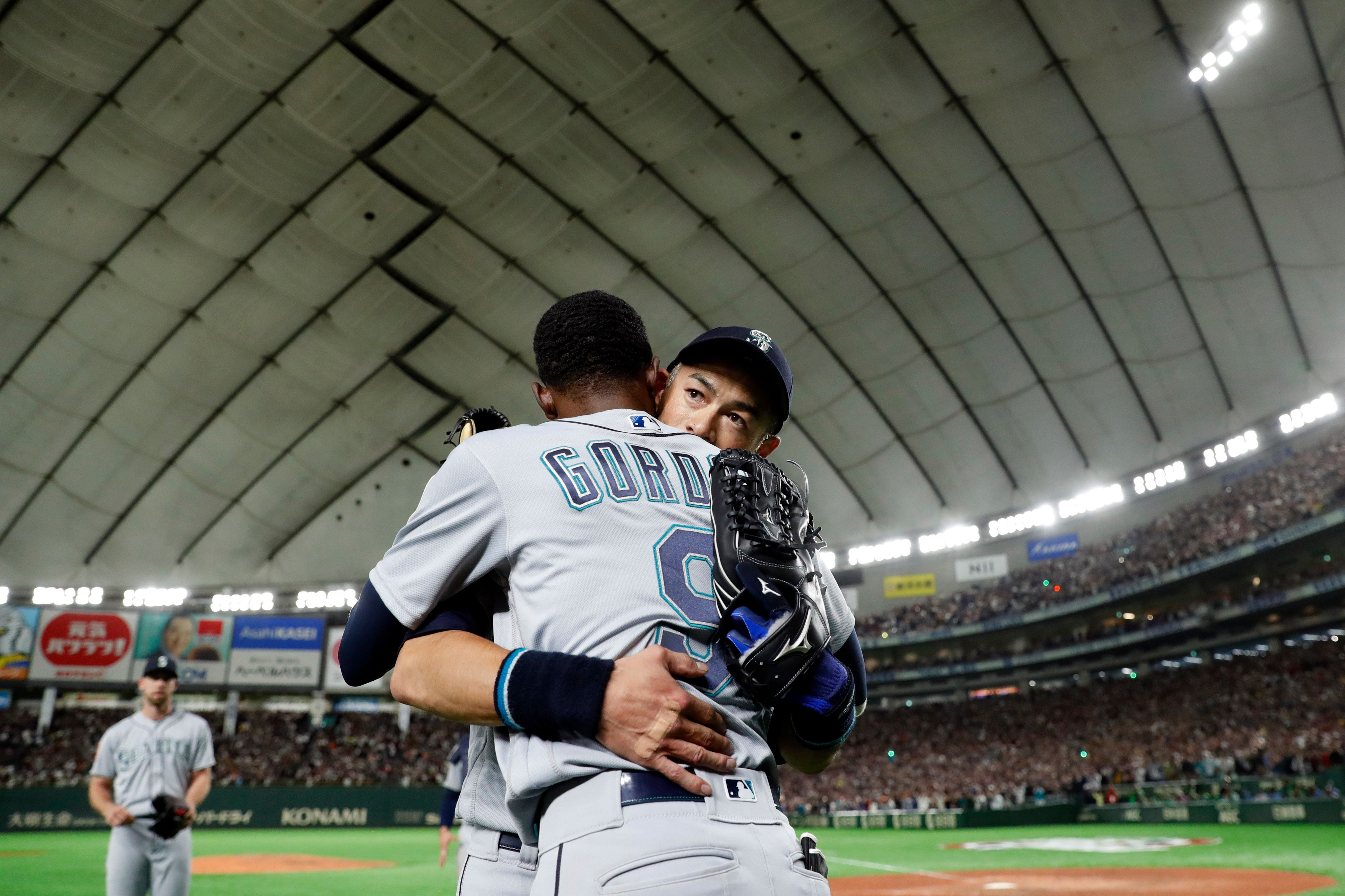 Ichiro Suzuki of the Seattle Mariners is greeted by teammate Dee Gordon after being taken out for a defensive replacement dur