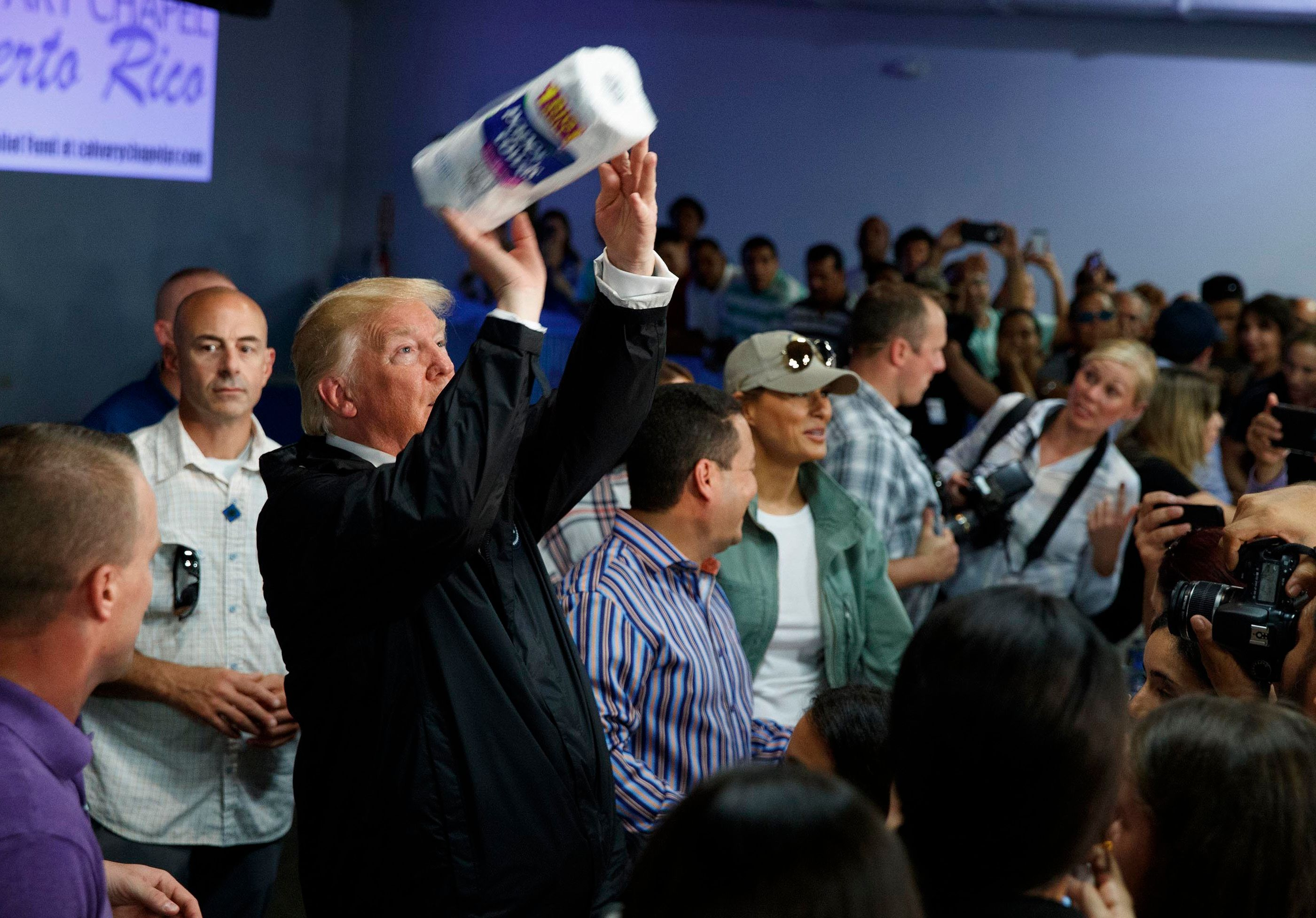 """FILE - In this Oct. 3, 2017 file photo, President Donald Trump tosses paper towels into a crowd at Calvary Chapel in Guaynabo, Puerto Rico. Trump congratulated Puerto Rico for escaping the higher death toll of """"a real catastrophe like Katrina"""" and heaped praise on the relief efforts of his administration without mentioning the sharp criticism the federal response has drawn. (AP Photo/Evan Vucci, File)"""