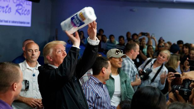 "FILE - In this Oct. 3, 2017 file photo, President Donald Trump tosses paper towels into a crowd at Calvary Chapel in Guaynabo, Puerto Rico. Trump congratulated Puerto Rico for escaping the higher death toll of ""a real catastrophe like Katrina"" and heaped praise on the relief efforts of his administration without mentioning the sharp criticism the federal response has drawn. (AP Photo/Evan Vucci, File)"
