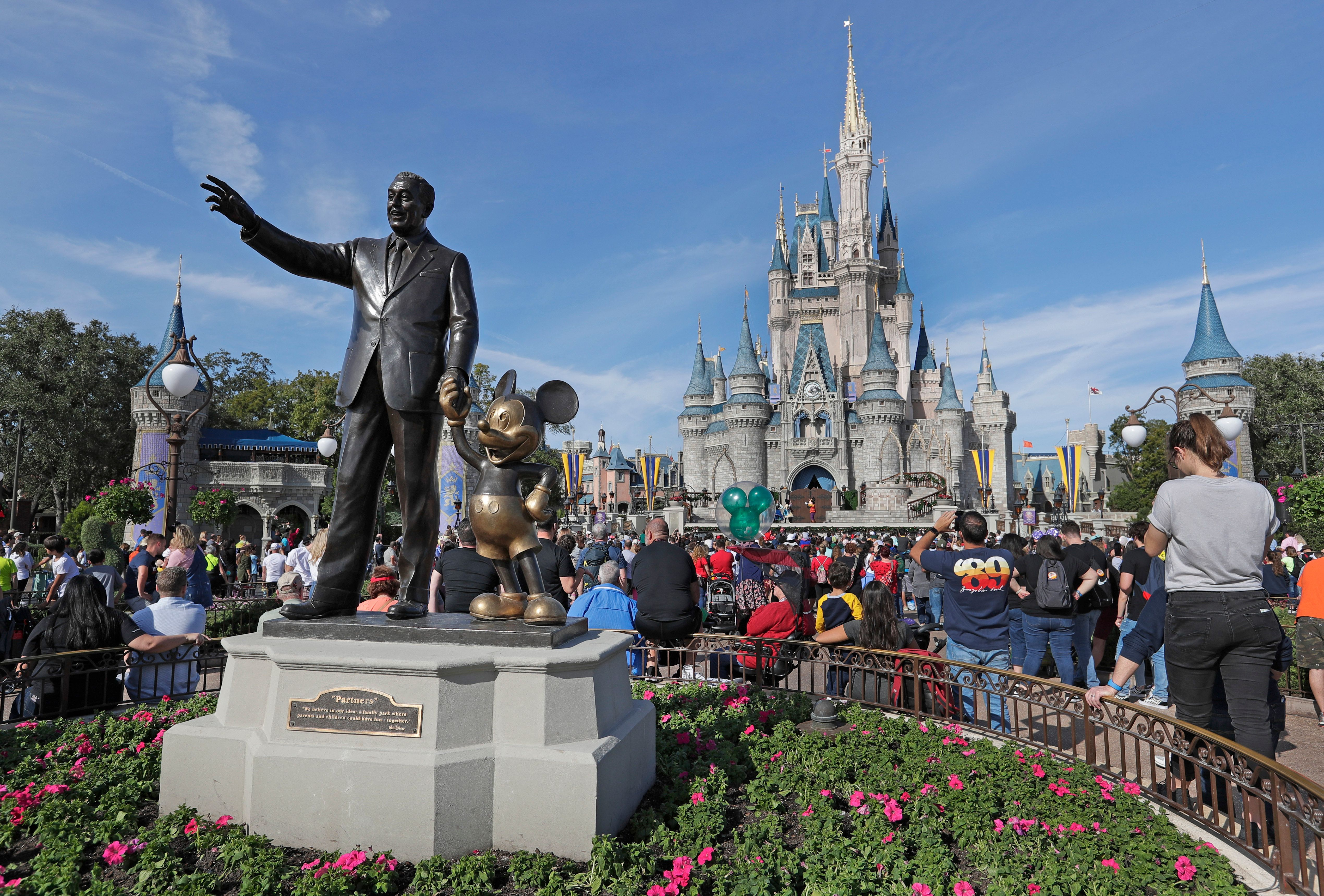 In this Wednesday, Jan. 9, 2019 photo near a statue of Walt Disney and Micky Mouse, guests at watch a show in front of the Cinderella Castle at the Magic Kingdom at Walt Disney World in Lake Buena Vista, Fla. (AP Photo/John Raoux)