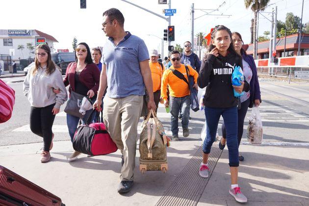 Pedestres caminham em direção à fronteira entre EUA e México, no Porto de...