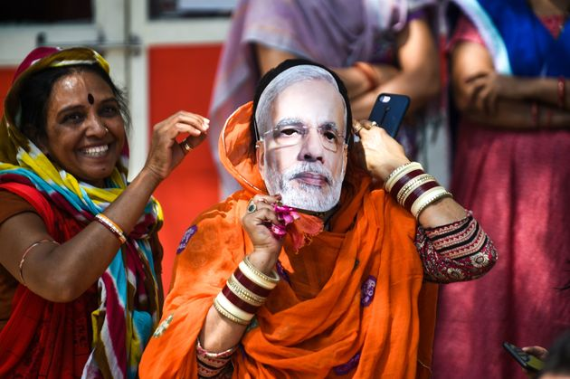 An Indian political supporter wears a mask of Indian Prime Minister Narendra Modi as she participates...