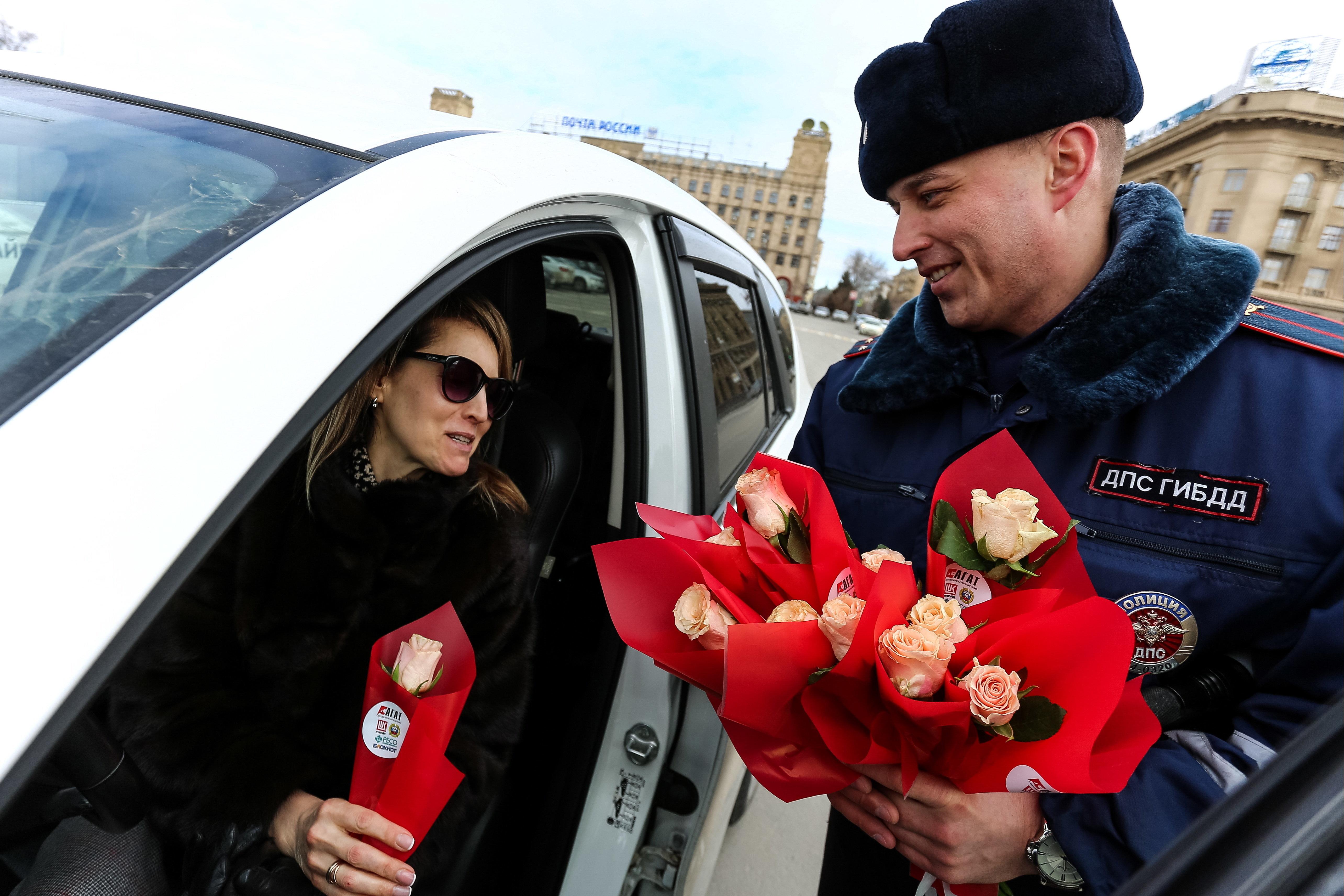 国際女性デーを記念して、通行する車の女性運転手(左)に花を贈る男性の交通警察官=3月7日、ロシア・ボルゴグラード