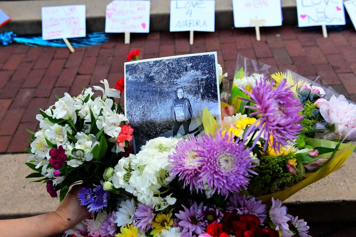 Friends, family, neighbors and strangers bring flowers to a vigil for Nabra Hassanen at Lake Anne Plaza near Reston, Virginia