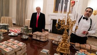 WASHINGTON, DC - JANUARY 14: (AFP OUT) U.S President Donald Trump watches as candles are lit as he presents fast food to be served to the Clemson Tigers football team to celebrate their Championship at the White House on January 14, 2019 in Washington, DC. (Photo by Chris Kleponis-Pool/Getty Images)