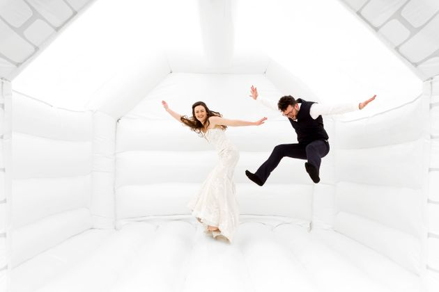 Tor and Duncan Cox jumping for joy in their wedding bouncy