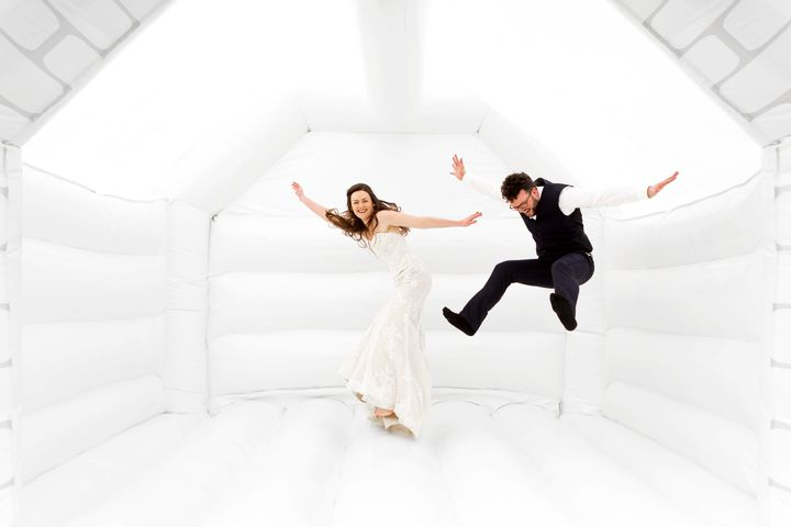 Tor and Duncan Cox jumping for joy in their wedding bouncy castle.