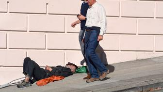 SAN FRANCISCO, CALIFORNIA - SEPTEMBER 16, 2018:  Two men walk past a homeless man sleeping on a sidewalk in San Francisco, California. (Photo by Robert Alexander/Getty Images)